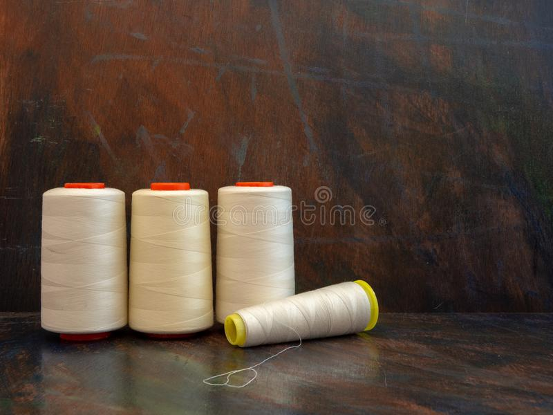 Industrial cones of white sewing threads on a dark background. Front view studio shot. royalty free stock photography