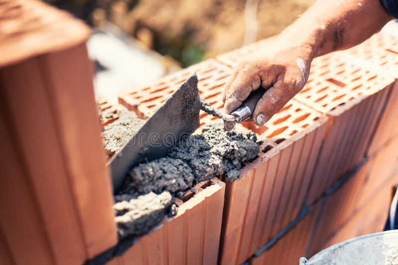 Industrial - Construction bricklayer worker building walls with bricks, mortar and putty knife. Industrial details - Construction bricklayer worker building royalty free stock photos
