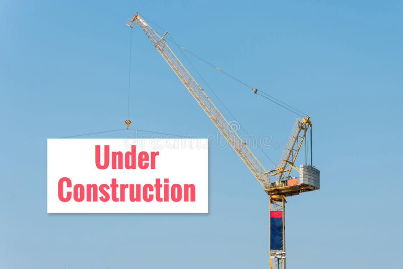 """Industrial Construction crane holding a billboard. With """"UNDER CONSTRUCTION' text on blue sky background. Elegant Design for advertisement and royalty free stock photography"""