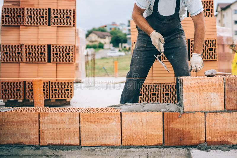 construction site details with worker laying bricks stock image
