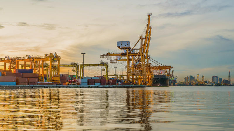 Industrial Container Cargo freight ship with working crane bridge in shipyard at dusk for Logistic Import Export background stock photography