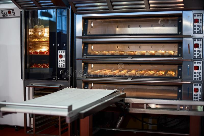 Industrial convection oven with cooked bakery products for catering. Professional kitchen equipment stock photography