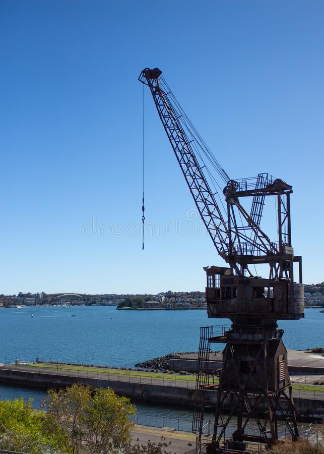 Industrial crane set dockside on Cockatoo Island Sydney Harbour Australia against blue water and sky. Industrial crane located dockside on Cockatoo Island Sydney royalty free stock images