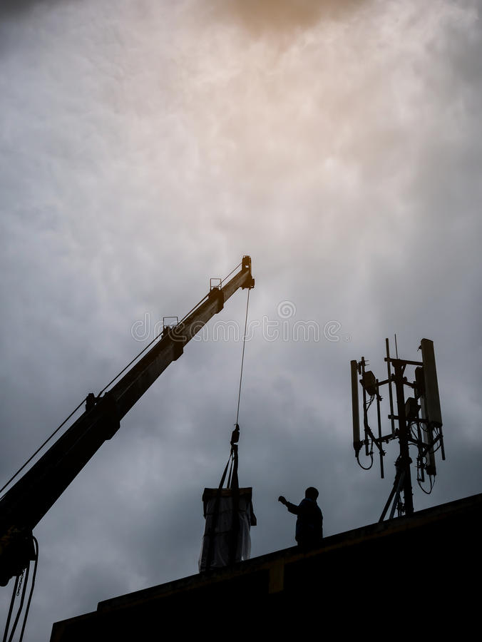 Industrial Crane operating and lifting electric box. Against clouds and sky with telecom tower royalty free stock images