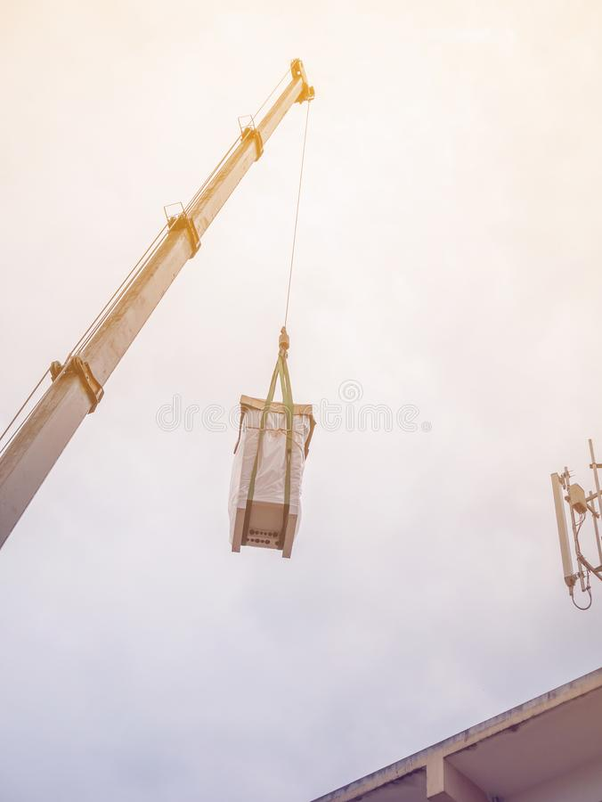 Industrial Crane operating and lifting electric box. Against clouds and sky with telecom tower stock images