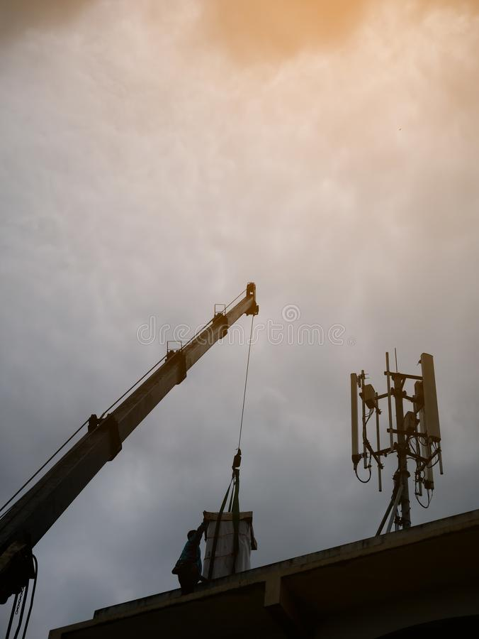 Industrial Crane operating and lifting electric box. Against clouds and sky with telecom tower royalty free stock photo