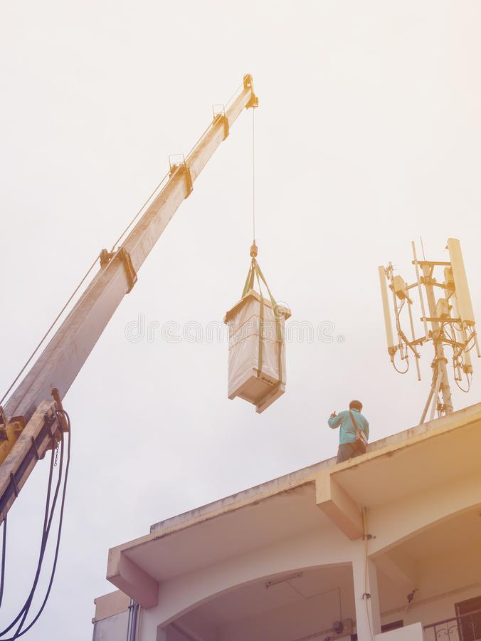 Industrial Crane operating and lifting electric box. Against clouds and sky with telecom tower stock photography