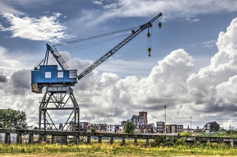 Industrial crane in urban redevelopment area. Empty lot with old crane and recently buildt appartment buildings in the background in the Staart urban stock photo