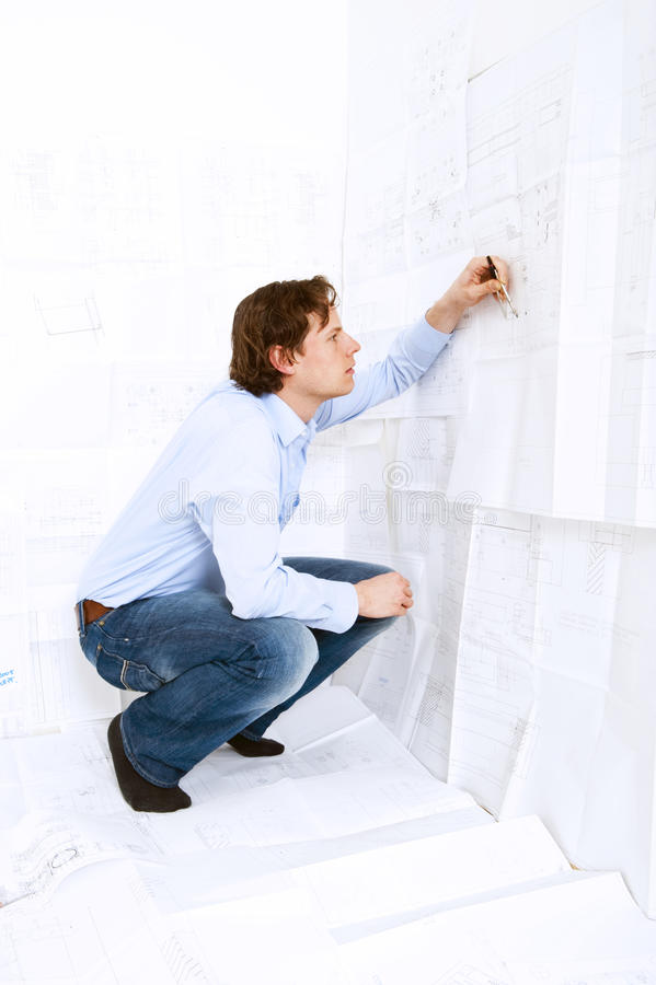 Industrial Design Engineer. Calculating measurements and tolerances on a technical drawing using a calculator stock image