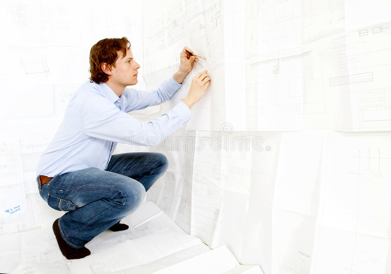 Industrial Design Engineer. An industrial design engineer checking technical drawings stock photo