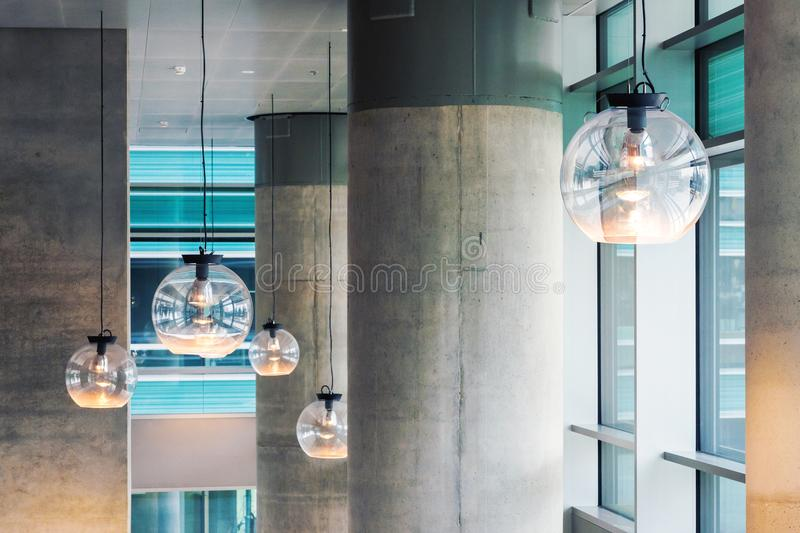 Industrial design interior with concrete pillars and ceiling lights stock images