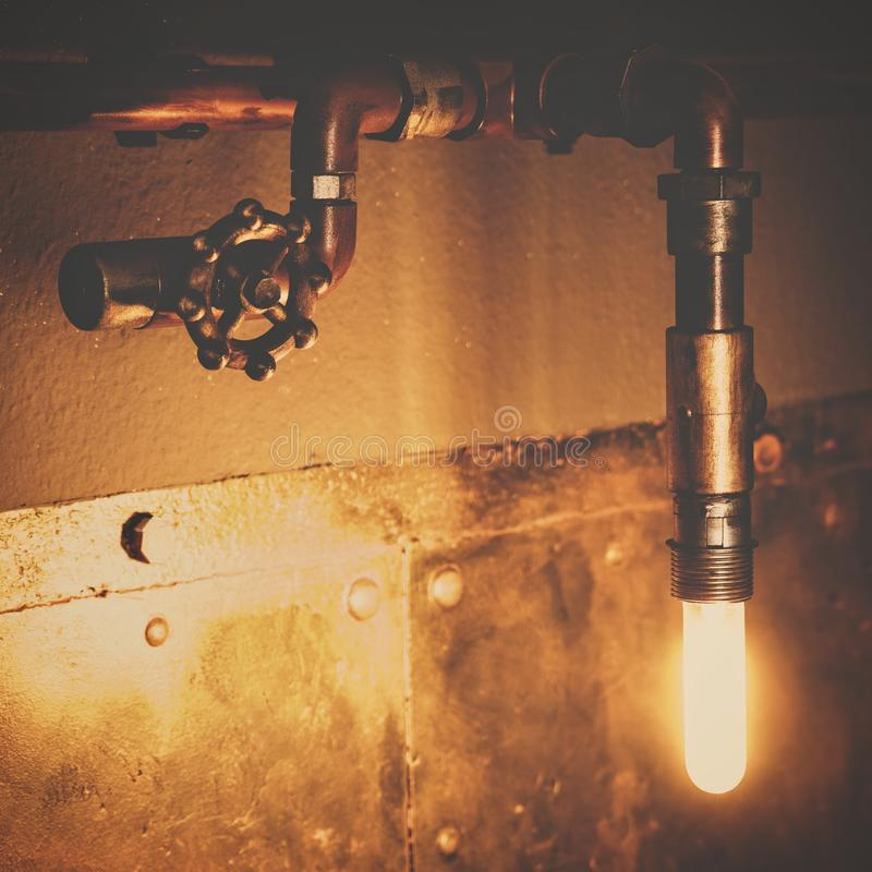 Industrial design lamp with pipes, valves and lightbulb, metallic interior decoration stock photo