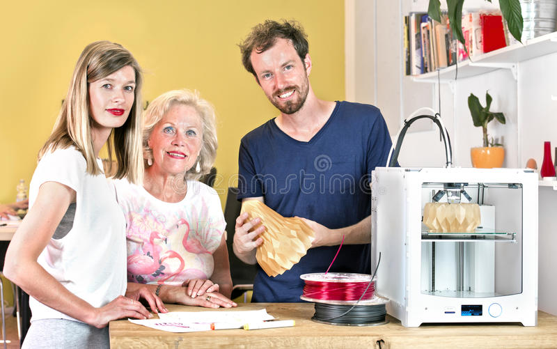 Industrial designers gathering around a 3D printer royalty free stock photo
