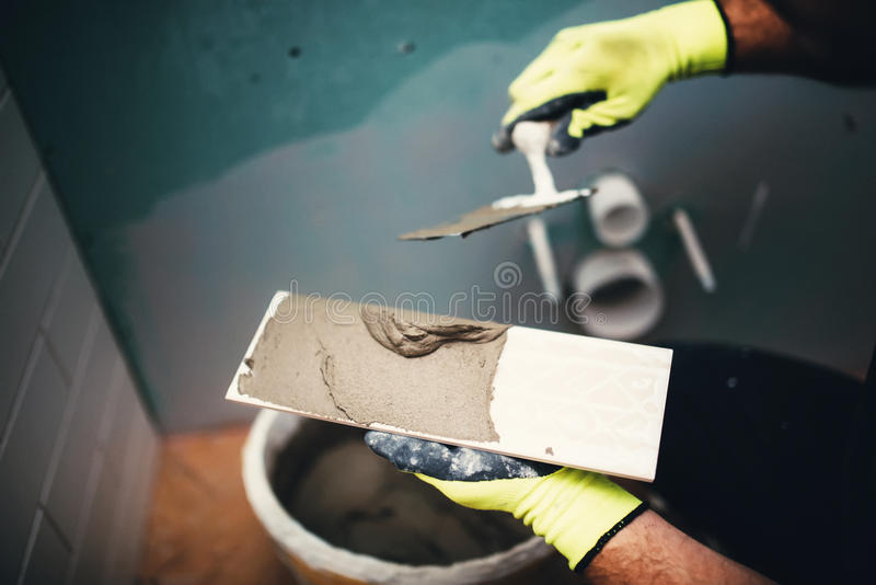 industrial detail of worker adding cement adhesive on small ceramic tiles stock image