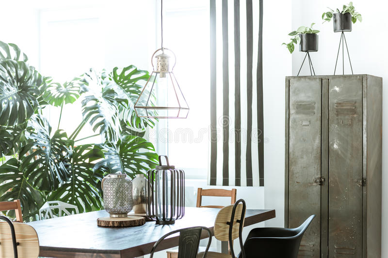 Industrial dining room with wardrobe. White, industrial dining room with metal wardrobe and wood table stock image