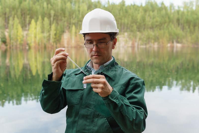 Industrial ecologist takes a sample of water from lake at the site of a flooded quarry. Industrial ecologist or chemist takes a sample of water from lake at the royalty free stock photos