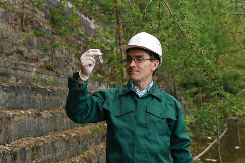 Industrial ecologist takes a sample of water from old quarry. Industrial ecologist or hydrologist takes a sample of water from old quarry stock image