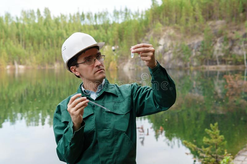 Industrial ecologist visually evaluates the response of a water sample from lake at the site of a flooded quarry. Industrial ecologist or hydrologist visually stock images