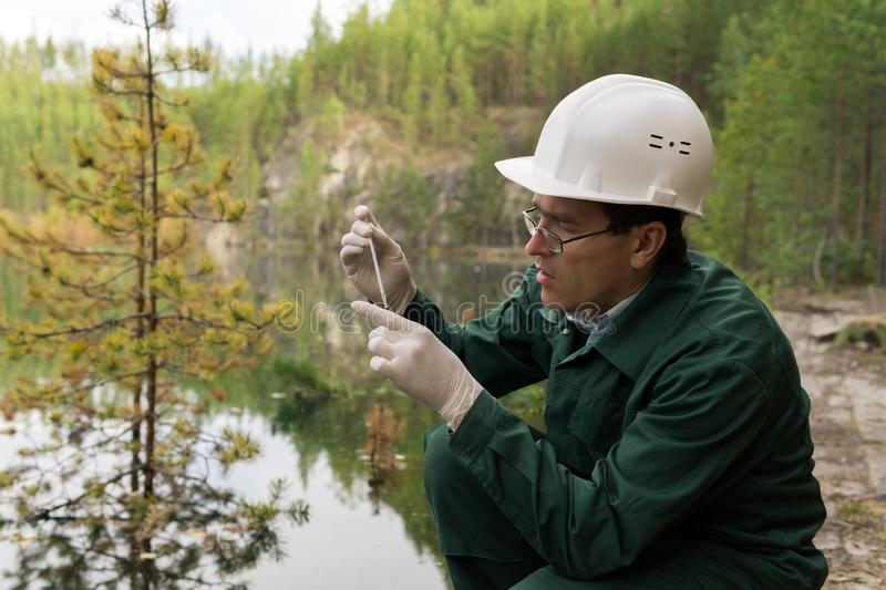 Industrial ecologist takes a sample of water from a flooded quarry. Industrial ecologist or chemist takes a sample of water from a flooded quarry stock image