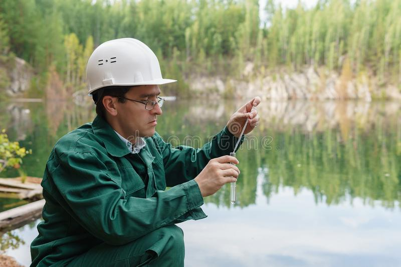 Industrial ecologist takes a sample of water from lake at the site of a flooded mining pit. Industrial ecologist or chemist takes a sample of water from lake at stock photography