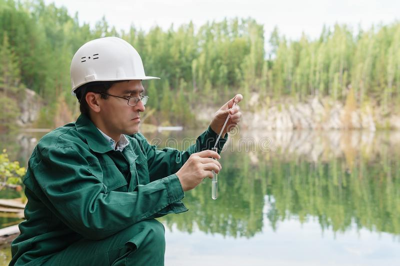 Industrial ecologist takes a sample of water from lake at the site of a flooded quarry. Industrial ecologist or chemist takes a sample of water from lake at the royalty free stock image