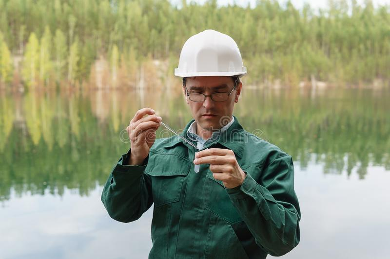 Industrial ecologist takes a sample of water from lake at the site of a flooded quarry. Industrial ecologist or chemist takes a sample of water from lake at the stock photos