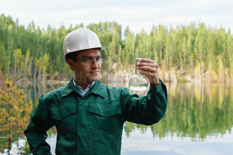 Industrial ecologist visually evaluates the response of a water sample from lake at the site of a flooded mining pit. Industrial ecologist or hydrologist stock photos