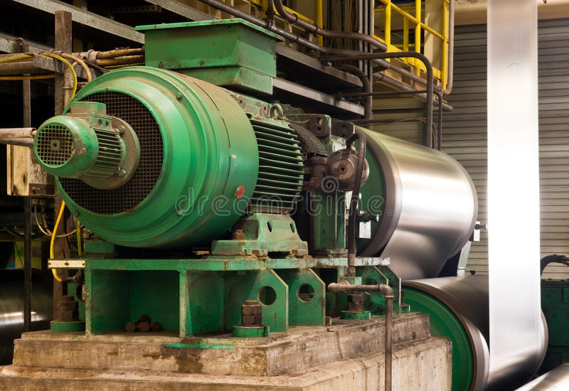 Industrial electric engine. Old electric engine powering a coil in a galvanised steel production line stock photo