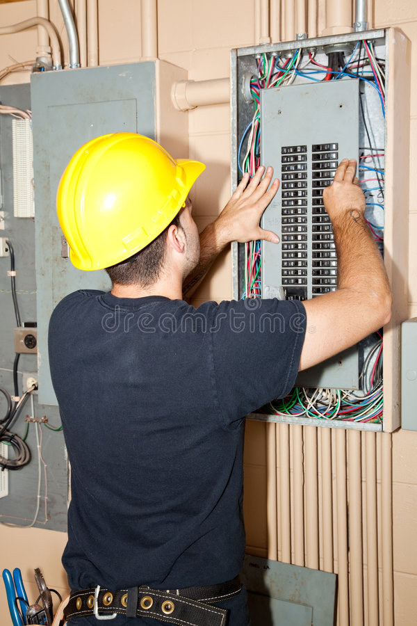 Industrial Electric Panel Repair. Electrician repairing circuit breakers in industrial electric panel stock images