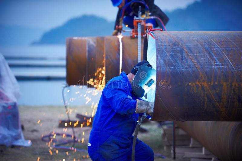 Industrial electrode welder with face shield and blue overall welding a steel pipe in workshop. E view stock images