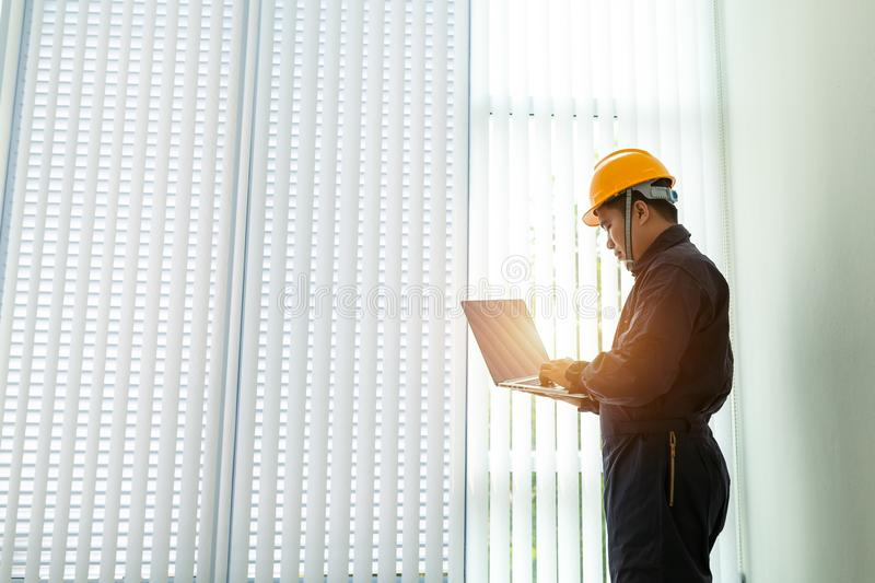 Industrial Engineer in Hard Hat Wearing Safety Jacket Uses Touchscreen Laptop. He Works at the Heavy Industry Manufacturing royalty free stock photo