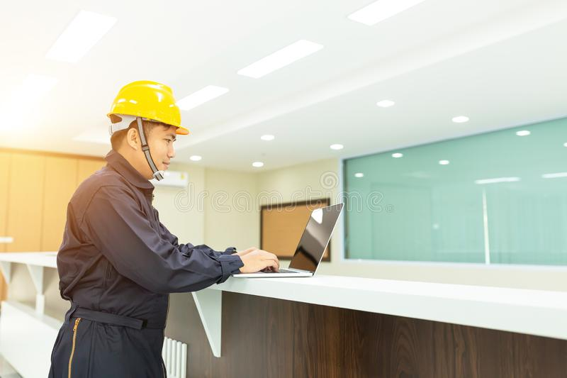 Industrial Engineer in Hard Hat Wearing Safety Jacket Uses Touchscreen Laptop. He Works at the Interior control stock photos