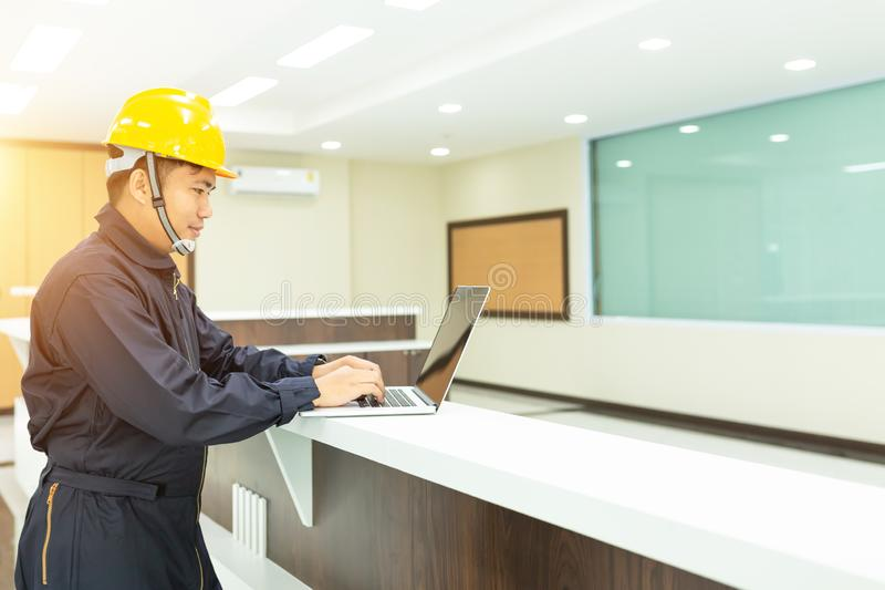 Industrial Engineer in Hard Hat Wearing Safety Jacket Uses Touchscreen Laptop. He Works at the Interior control stock photography