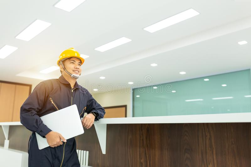 Industrial Engineer in Hard Hat Wearing Safety Jacket Uses Touchscreen Laptop. He Works at the Interior control royalty free stock photo