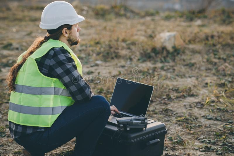 Industrial Engineer in Hard Hat Wearing Safety Jacket Uses Touchscreen Laptop. He Works at the Windmill Factory. Factory stock photo