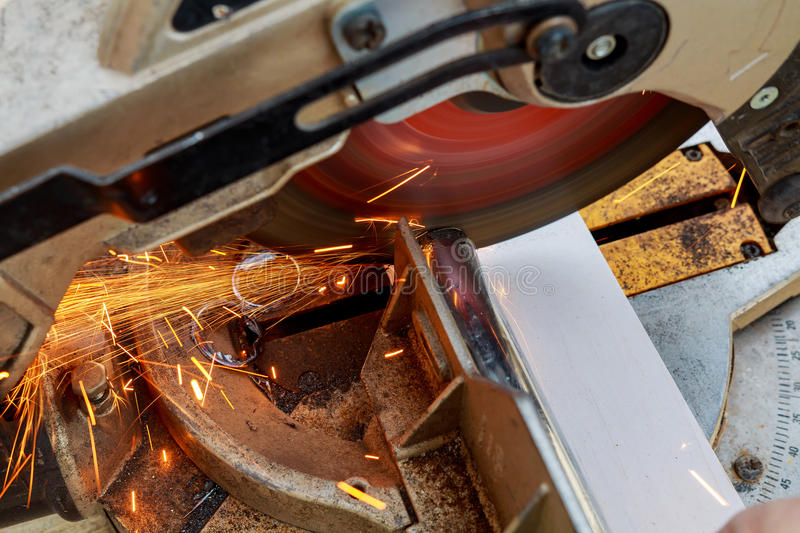 industrial engineer working on cutting a metal and steel with compound mitre saw sharp, circular blade royalty free stock images