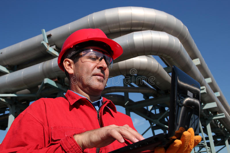 Industrial Engineer Working on a Notebook Computer Outdoor. Industrial engineer inside oil and gas refinery using notebook royalty free stock image