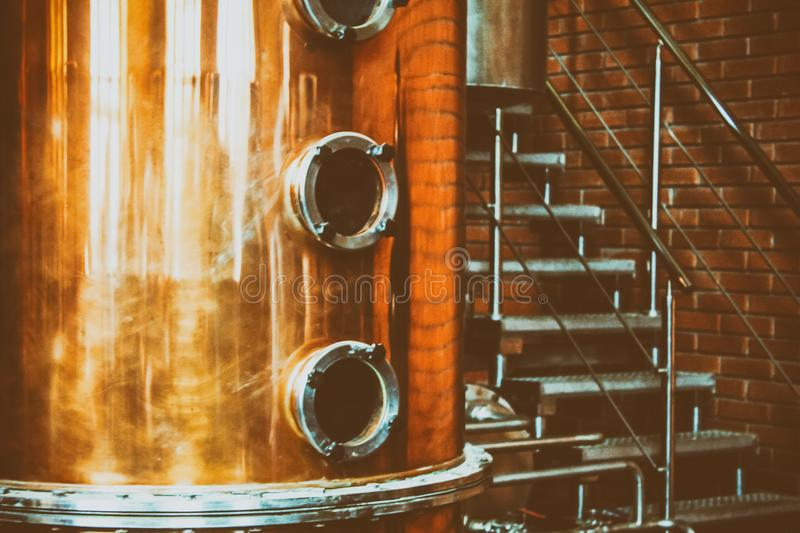 Industrial equipment for brandy production. Copper still alembic inside distiller to distill grapes and produce spirits. Noises and large grain - stylization stock image