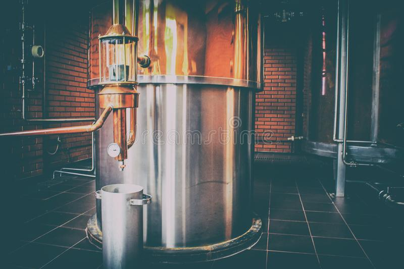 Industrial equipment for brandy production. Copper still alembic inside distiller to distill grapes and produce spirits. Noises and large grain - stylization royalty free stock images