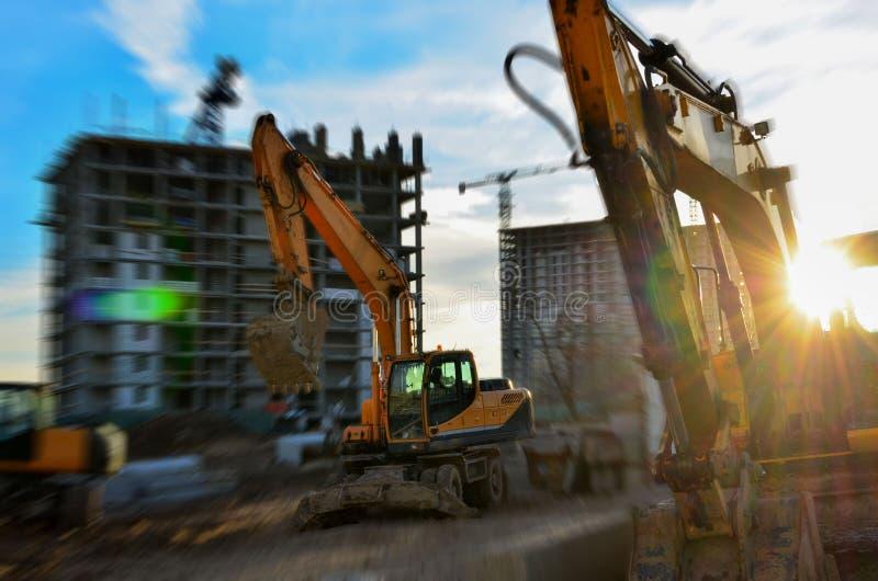 Industrial equipment, earthmoving excavators and construction crane at sunset, sunrise. Blur effect. Under construction site - Image stock image