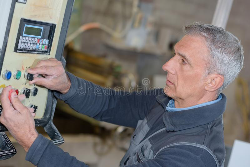 Industrial factory worker operates machine stock photo