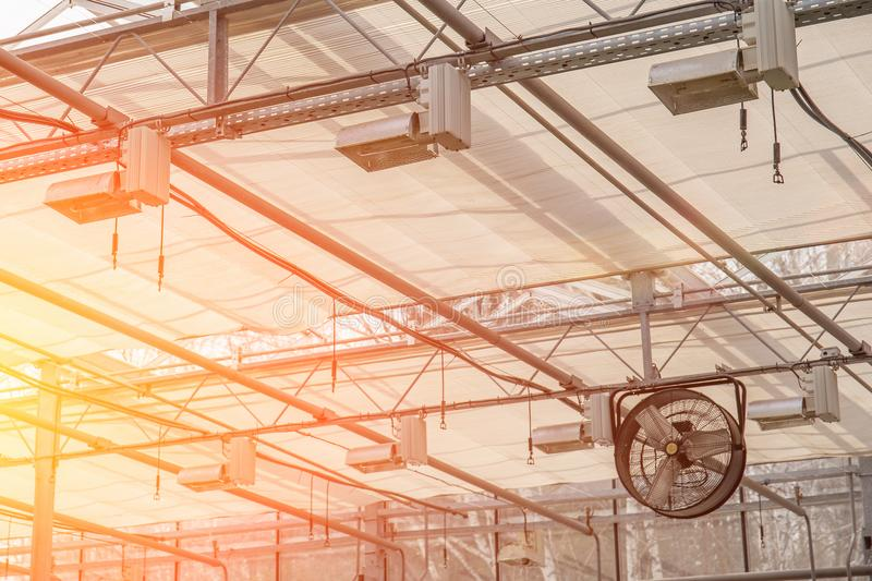 Industrial fan inside modern greenhouse, electric automation ventilation system inside glasshouse. Toned stock photo