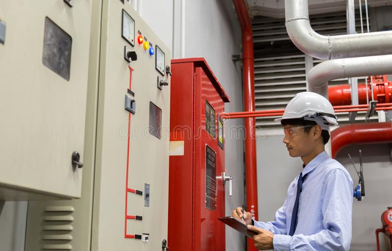 Engineer with tablet check red generator pump for water sprinkler piping and fire alarm control system. Industrial fire control system,Fire Alarm controller royalty free stock photography