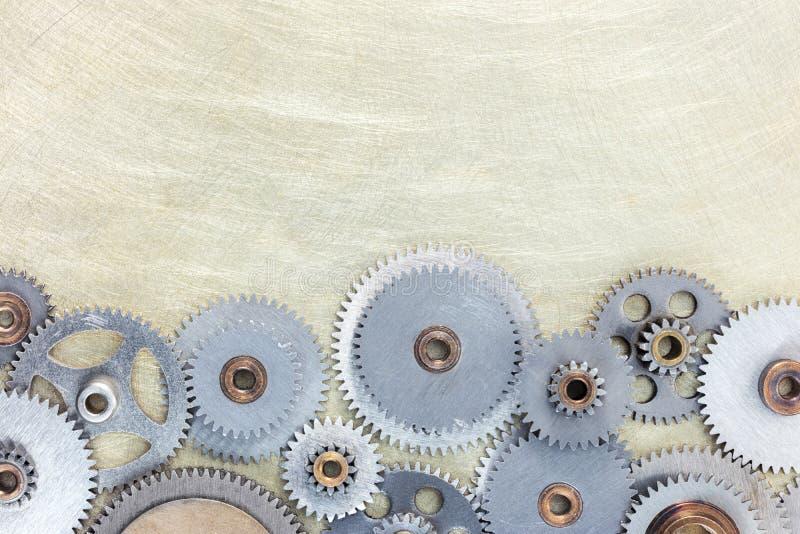 Industrial gear cogwheels on scratched brass metal surface. Industrial gear cogwheels on scratched brass metal background stock image