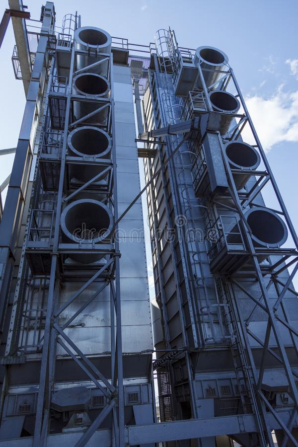 Industrial grain cereal drying machine with huge air vents. Industrial grain cereal drying machine with huge circular air vents, and a blue sky stock images