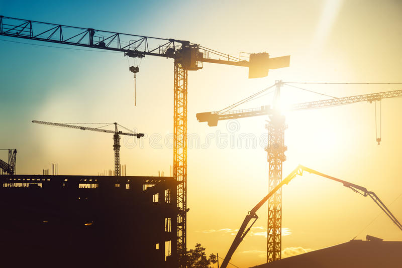 Industrial heavy duty construction site with tower cranes and building silhouettes stock images