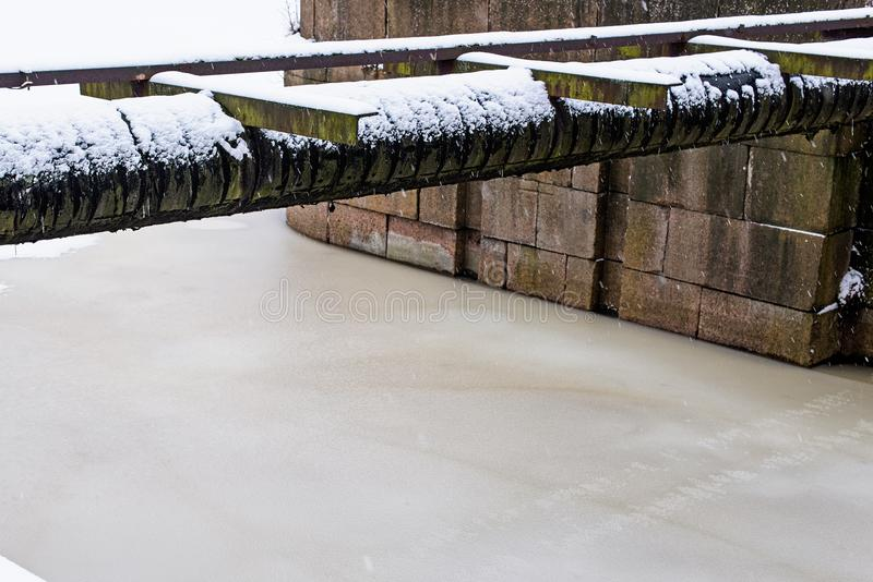Industrial horizontal pipe over a frozen river. Industrial pipe over a frozen river stock photos