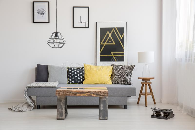 Industrial interior with wooden table. Simple, industrial interior design of living room with wooden table standing in front of a gray sofa with yellow and black stock photos