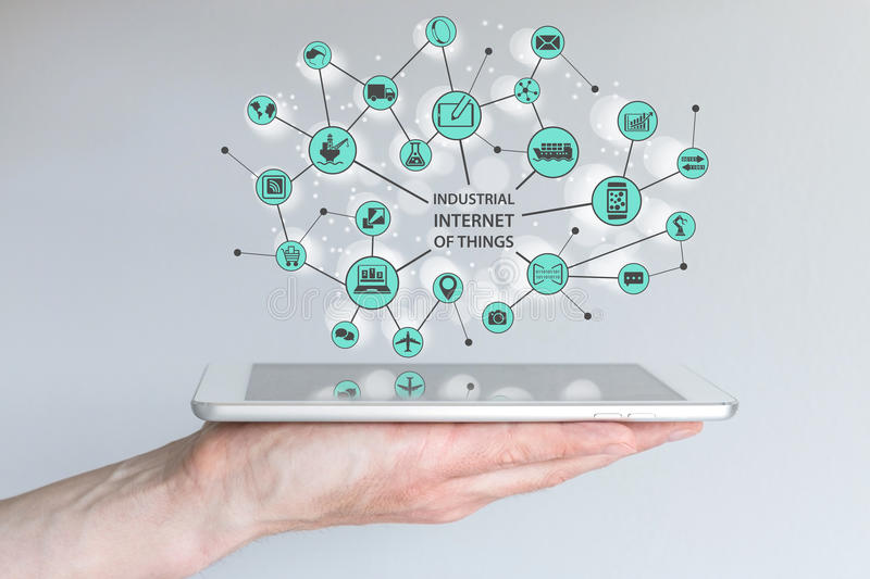 Industrial internet of things IOT concept. Male hand holding modern smart phone or tablet. With illustration of connected things and objects