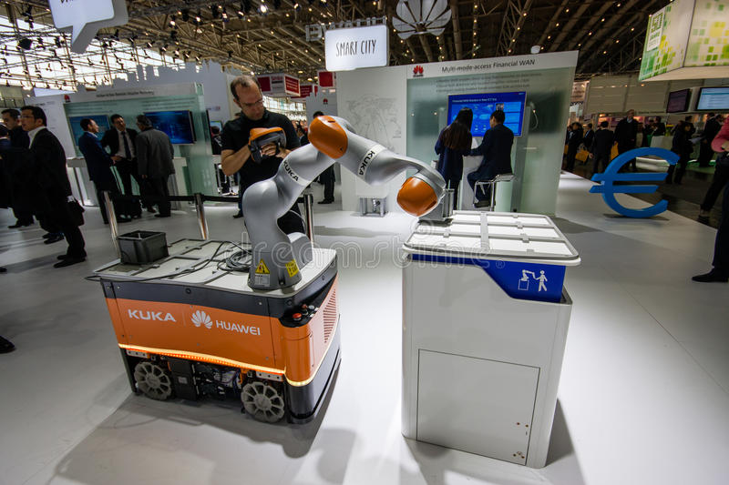 Industrial KUKA robot in booth of Huawei company at CeBIT. HANNOVER, GERMANY - MARCH 14, 2016: Industrial KUKA robot in booth of Huawei company at CeBIT royalty free stock image